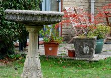 Ornate bird bath with plants and garden chairs