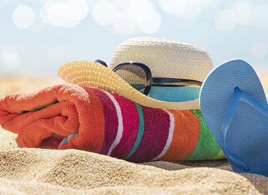 Towel, Hat, Sunglasses and flip flops on a beach