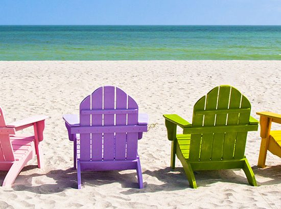 Row of coloured chairs on a snady beach with the sea in the background