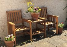 Summer chairs with flowers in plant pots